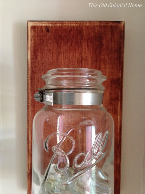 Attach mason jar to wood with pipe clamp
