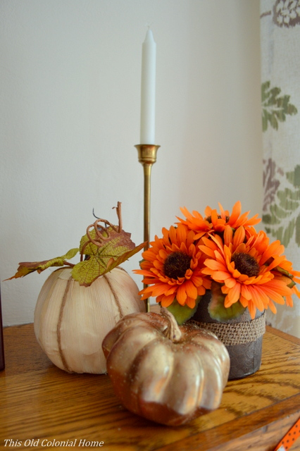 Pumpkins, flowers and candle on mantel
