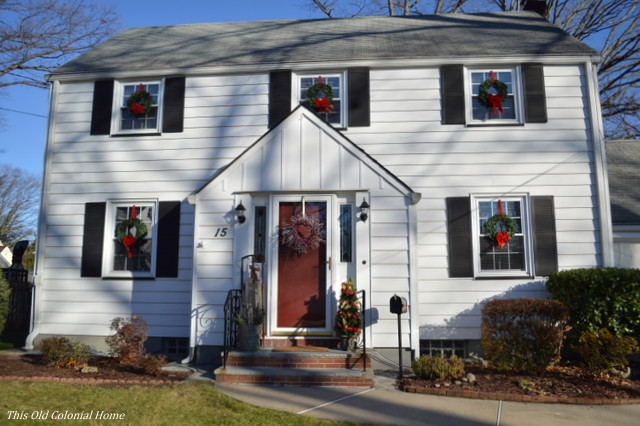 Christmas wreaths displayed in house windows