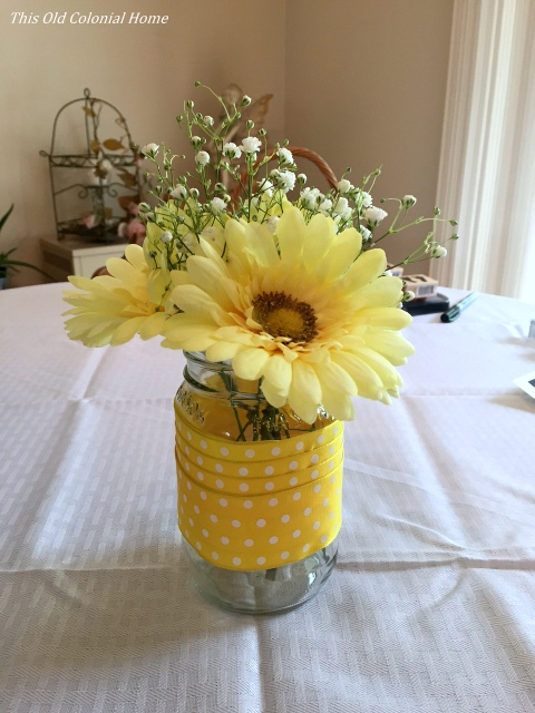 Yellow mason jar centerpiece with ribbon